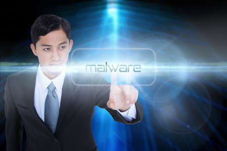 unsmiling: The word malware and unsmiling asian businessman pointing against shiny arrow lines on black background