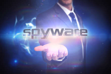 spyware: The word spyware and businessman presenting against glowing technological background