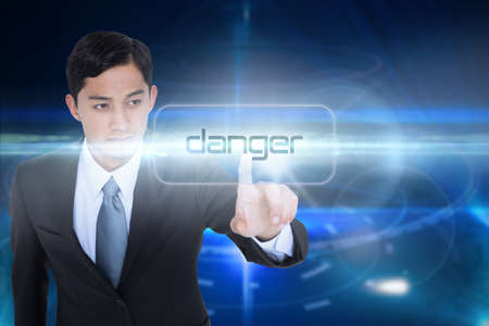 unsmiling: The word danger and unsmiling asian businessman pointing against futuristic black background with circles