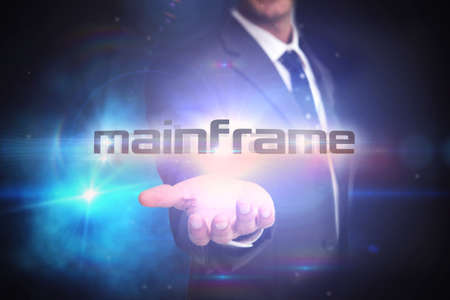 mainframe: The word mainframe and businessman presenting against black background with glowing light LANG_EVOIMAGES