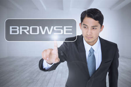 unsmiling: The word browse and unsmiling asian businessman pointing against big room with white wall LANG_EVOIMAGES