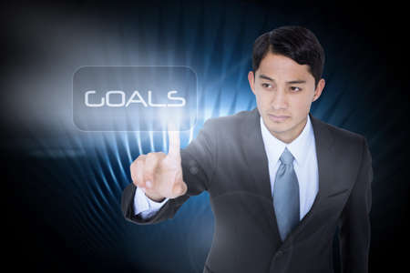 unsmiling: The word goals and unsmiling asian businessman pointing against black glowing design
