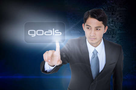 unsmiling: The word goals and unsmiling asian businessman pointing against futuristic background with circuit board
