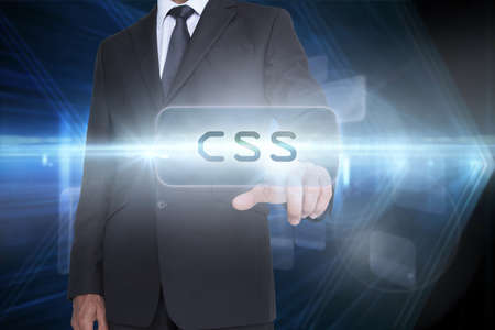 css: The word css and businessman pointing against shiny arrow lines on black background