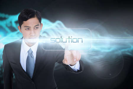 against abstract: The word solution and unsmiling asian businessman pointing against abstract blue glowing black background LANG_EVOIMAGES