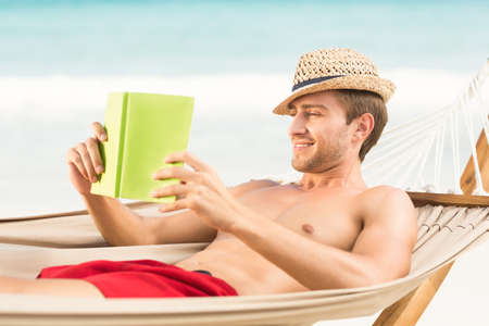 escapism: Handsome man reading on the hammock at the beach