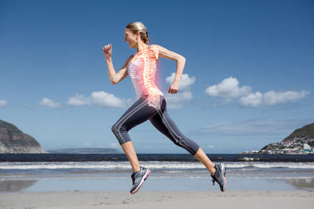 bone health: Digital composite of Highlighted back bones of jogging woman on beach