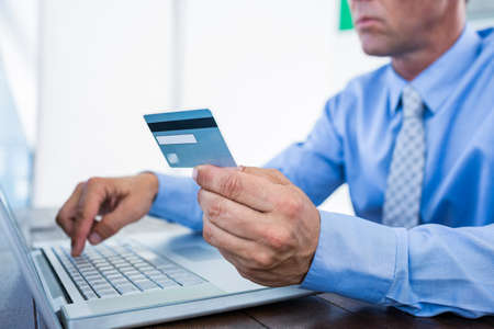 holding credit card: Businessman using laptop computer and holding credit card in office