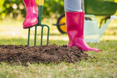 gum boots: Woman wearing pink rubber boots working in the garden with a pitch fork
