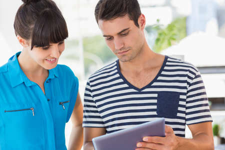 casual business: Casual business team looking at tablet together in creative office