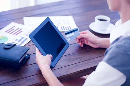 holding credit card: Businesswoman using tablet pc and holding credit card in office
