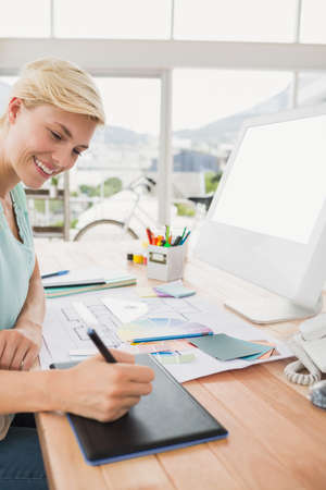 graphic tablet: Smiling creative businesswoman writing on graphic tablet in the office