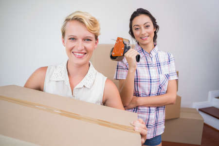 sealing tape: Lesbian couple holding cardboard boxes and tape sealing