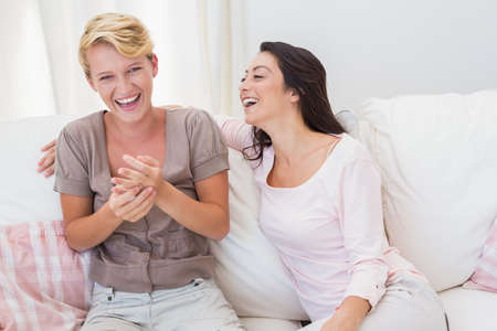 homosexual partners: Smiling homosexual couple sitting on couch and laughing at an apartment