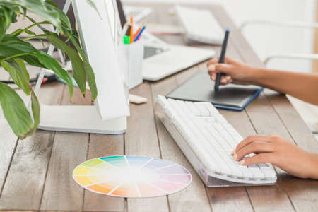 graphics tablet: Graphic designer using a graphics tablet in her office