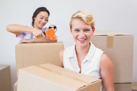 sealing: Lesbian couple holding cardboard boxes and using tape sealing LANG_EVOIMAGES