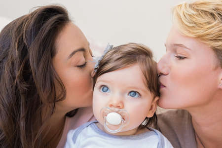Close up view of a lesbian couple kissing their baby girl