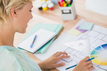 over the shoulder: Over shoulder view of smiling creative businesswoman drawing plans LANG_EVOIMAGES