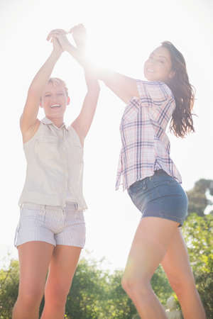 homosexual partners: Portrait of a lesbian couple with hands up in the air
