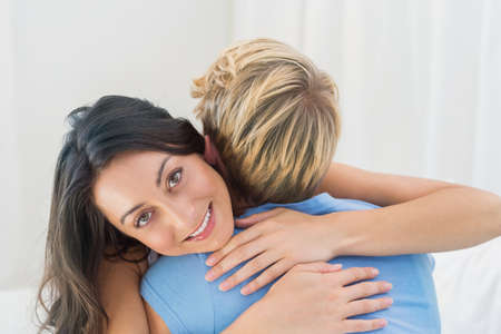 couple on couch: Smiling homosexual couple sitting on couch and embracing at an apartment