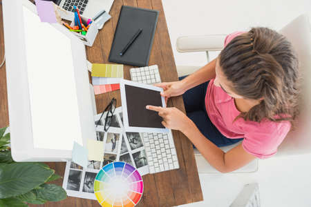 high angle: High angle of creative businesswoman using tablet in the office LANG_EVOIMAGES