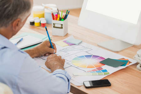 over the shoulder view: Over shoulder view of creative businessman drawing plans using colour watch