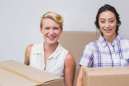 homosexual partners: Portrait of a lesbian couple holding cardboard boxes LANG_EVOIMAGES