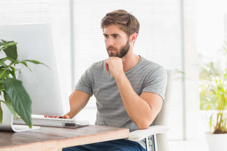 swivel chairs: Handsome businessman sitting on a swivel chair and using his laptop in the office