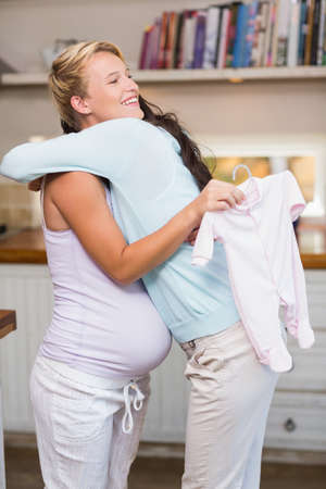 pregnant blonde: Side view of a pretty pregnant blonde hugging a friend