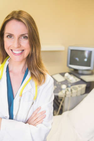 prenatal care: Young smiling doctor looking at camera at the ultrasound clinic