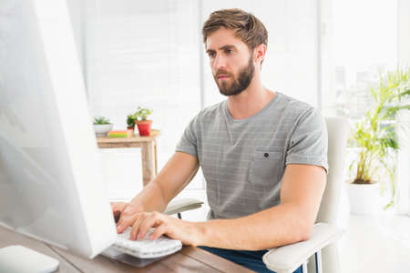 swivel chair: Handsome businessman sitting on a swivel chair and using his laptop in the office