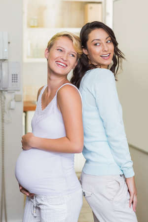 giving back: Smiling lesbian pregnant couple giving back to back