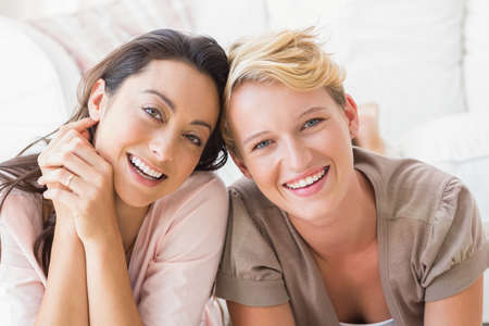 homosexual partners: Portrait of smiling homosexual couple looking at camera at an apartment