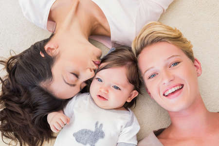 Portrait of a lesbian couple lying with their baby girl