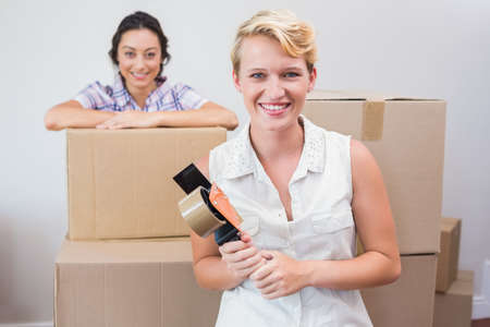 sealing: Smiling lesbian couple holding a tape sealing in an empty room