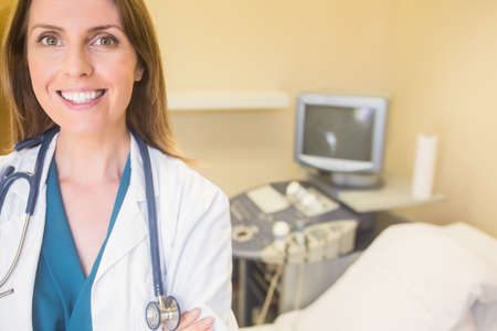 obstetrician: Young smiling doctor looking at camera at the ultrasound clinic