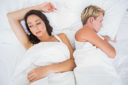 troubled: Troubled woman lying next to her sleeping girlfriend in bed LANG_EVOIMAGES