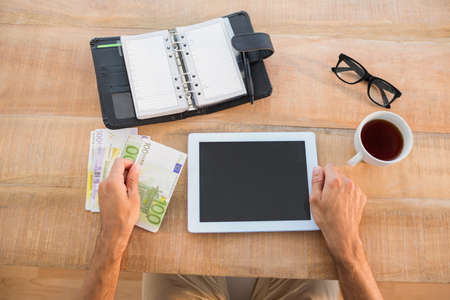 bank notes: Man using tablet and holding bank notes on wooden table in the office LANG_EVOIMAGES