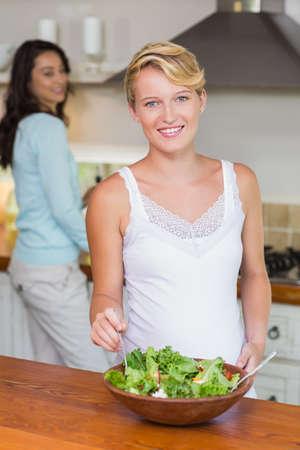homosexual partners: Portrait of a smiling pregnant woman preparing fresh salad