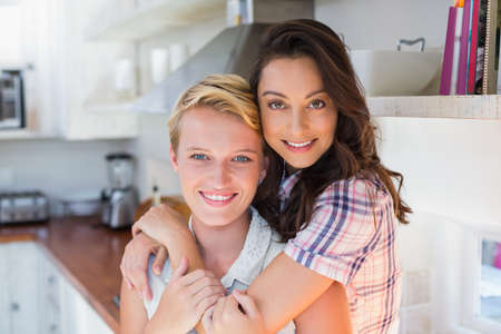 arms around: Portrait of a smiling lesbian couple with arms around