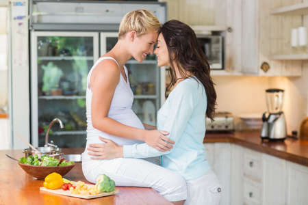 lesbian love: Pregnant lesbian couple giving head to head in the kitchen