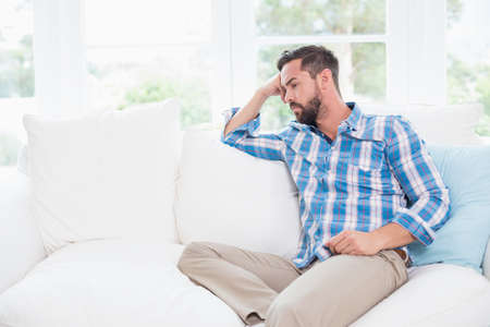 pounding head: Unhappy man suffering from migraine lying in the sofa
