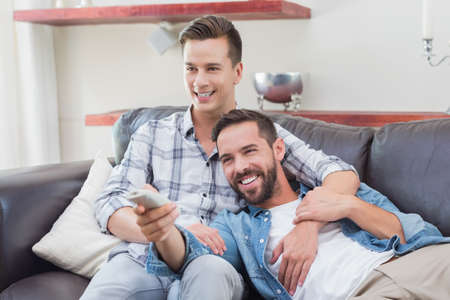 changing channel: Homosexual couple men watching television together holding the remote control