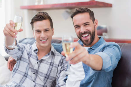 champagne flute: Portrait of homosexual couple men toasting with a champagne flute