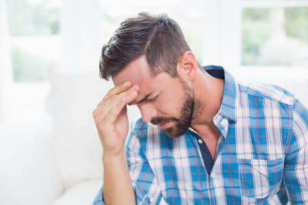 wincing: Ill man suffering from headache touching his forehead