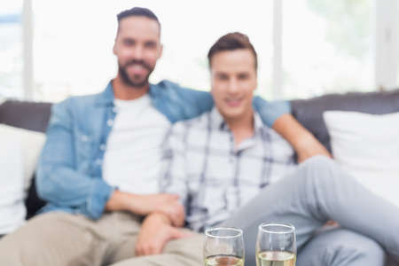champagne flutes: Homosexual couple men reading a book with two champagne flutes ahead