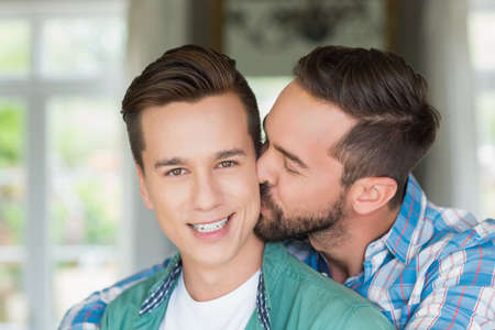 hombres besandose: Smiling homosexual couple men kissing each other LANG_EVOIMAGES