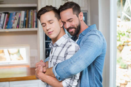 eye closed: Homosexual couple men with arms around and eye closed