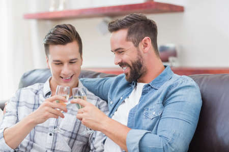 champagne flute: Smiling homosexual couple men toasting whith a champagne flute