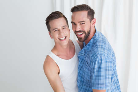 romantic man: Happy homosexual couple looking at camera at home LANG_EVOIMAGES